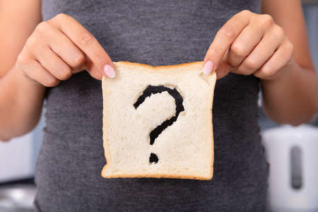 Mid-section Of A Woman Hands Holding Sliced Bread With Question Mark Sign