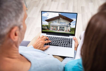 Couple Looking At House Online On Laptop At Home
