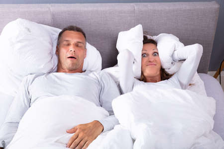 Mature Woman Covering Her Ears With Cushion While Man Snoring In Bed