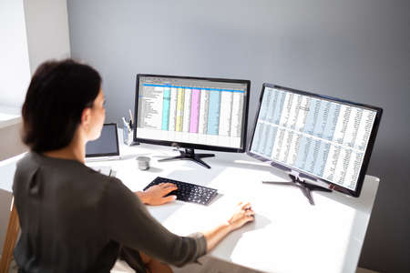 Side View Of Businesswoman's Hand Analyzing Data On Computer Over Desk