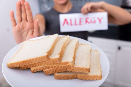 Young Woman Refusing Bread Slice On Plate At Home Holding Allergy Text Card
