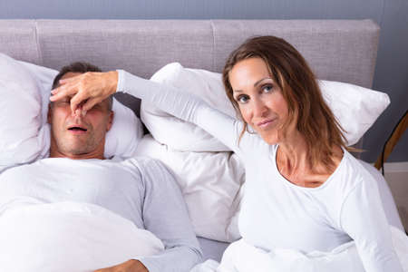 Disturbed Mature Woman Holding Her Husband's Nose To Stop Him From Snoring On Bed Standard-Bild