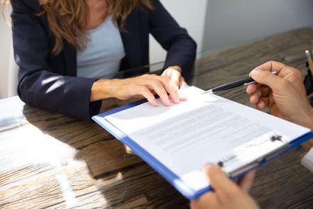 Primo piano di un agente immobiliare che aiuta il cliente nella compilazione del modulo di contratto Archivio Fotografico
