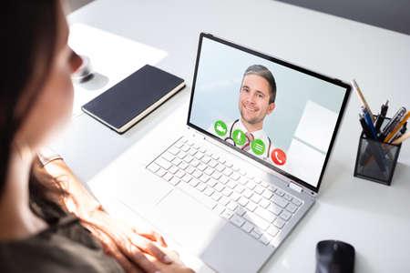 Young Female Video Chatting With Doctor On Laptop