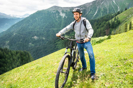 Main On Mountain With His Bike In Alps 免版税图像