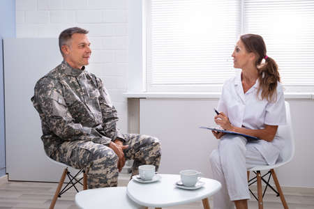 Female Psychologist Writing Down Notes During Counseling Session With Army Officer