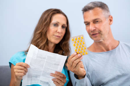 Matured Couple Sitting On Sofa Reading A Leaflet After Taking Pills At Home