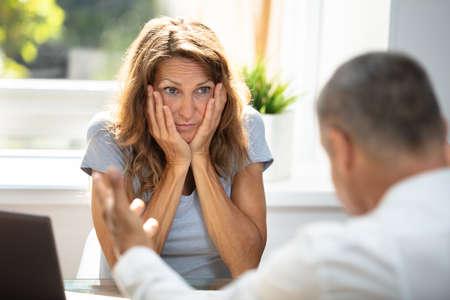 Unglückliche Frau, die ihren Kollegen anschaut, während sie im Büro sitzt