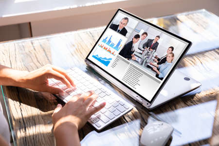 Cropped Image Of Businesswoman Using Laptop At Desk For Video Conferencing