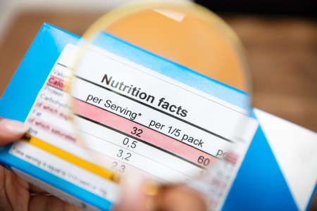 Woman Looking Nutrition Facts On Food Box Through Magnifying Glass Stockfoto