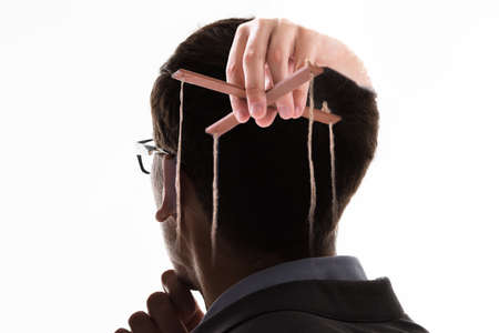 A Businessmans Hand Manipulating Marionette With String Against White Background