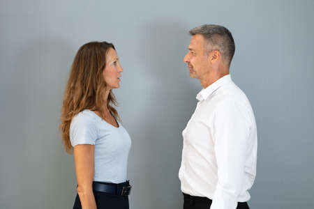 Two Businesspeople Looking At Each Other In Front Of Grey Background