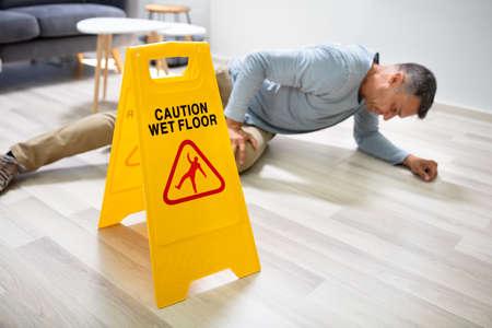 Hombre maduro cayendo sobre suelo mojado delante del cartel de precaución en casa