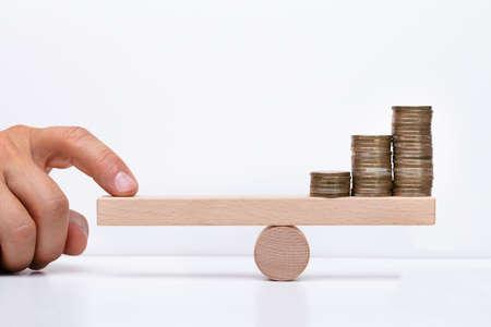 Nahaufnahme der Hand eines Unternehmers, die gestapelte Münzen auf hölzerner Wippe mit dem Finger über dem Schreibtisch balanciert Standard-Bild