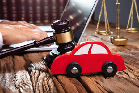 Red Car In Front Of Gavel And Mallet And Businessperson Using Laptop