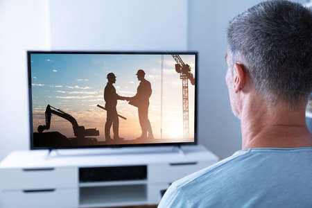 Rear View Of Man Watching Television At Home Imagens