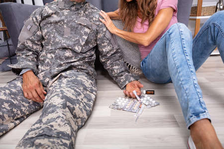 Disabled Veteran Sitting On Floor With Syringe And Pills Near His Wife Supporting Him Reklamní fotografie