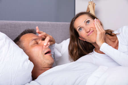 Frustrated Mature Woman Trying To Stop Man's Snoring With Her Finger While Sleeping On Bed Standard-Bild