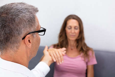 Close-up Of Professional Hypnotherapist Holding Woman Hand During Hypnotherapy