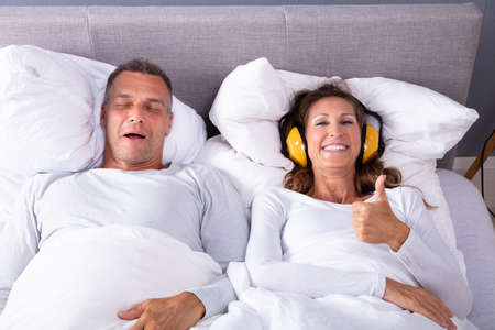 Happy Mature Woman Covering Her Ears With Headphone Showing Thumb Up Sign While Man Snoring