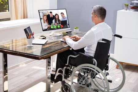 Uomo d'affari disabile seduto sulla sedia a rotelle e utilizzando il computer in ufficio Archivio Fotografico