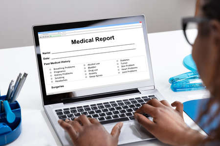 African Female Filling Patient Information Form On Digital Laptop Over White Desk