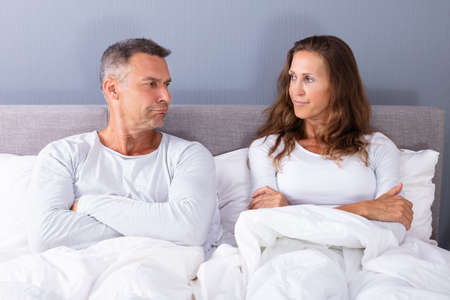 Portrait Of Sad Couple Sitting On Bed With White Blanket