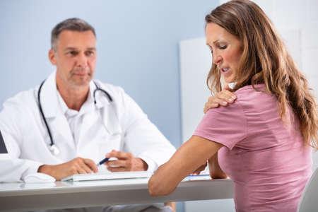 Médico maduro mirando paciente femenino mostrando su hombro dolorido en la clínica