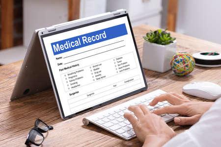Female Doctor Filling Patient Information Form On Digital Laptop Over Wooden Desk