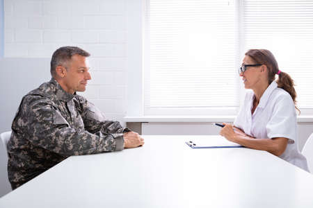 Female Doctor And Worried Military Officer Discussing About Problems He Has During Psychotherapy Treatment