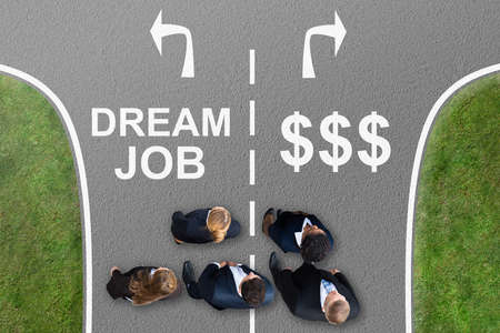 Businesspeople Standing On Street With Arrow Sign Showing Dream Job And Dollar Sign Direction