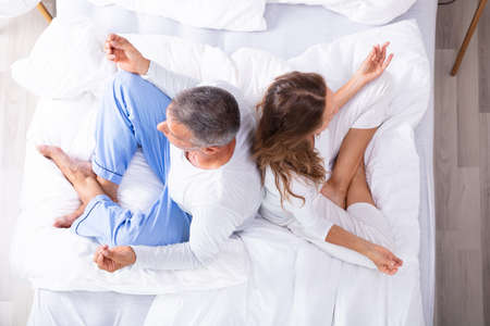 Matured Couple Sitting Back To Back On Bed Meditating Фото со стока