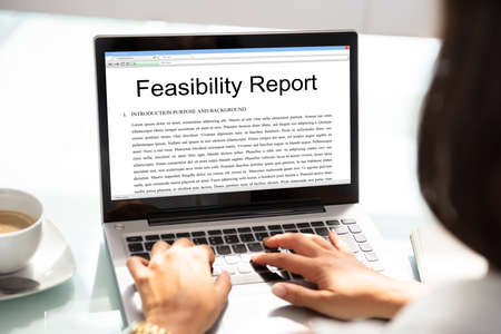 Businesswoman Typing On Laptop With Feasibility Report On Screen In Office Stockfoto