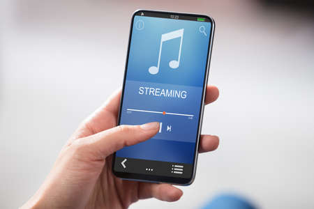 Close-up Of Persons Hand Holding Smartphone With Music Streaming On Screen