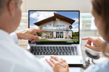Rear View Of Two Businesspeople Looking At House On Laptop Reklamní fotografie