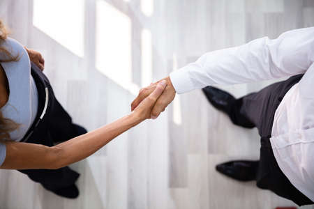 An Elevated View Of Businessman Shaking Hands With His Partner In Office