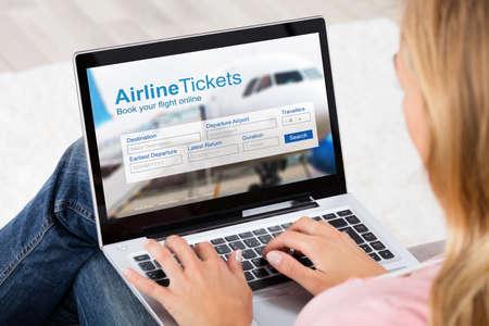 Donna che prenota biglietti aerei online utilizzando il laptop digitale a casa