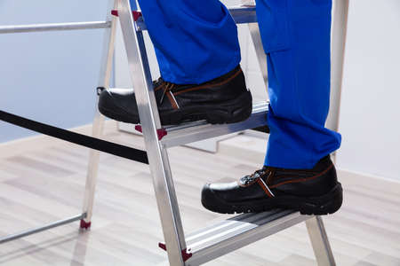 Low Section View Of A Handymans Foot Climbing Ladder