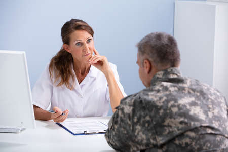 Close-up Of Depressed Army Soldier Suffering From Ptsd During Psychotherapy Session At Doctors Clinic