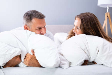 Happy Couple Relaxing On Bed With White Pillow Фото со стока