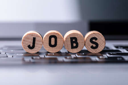 Close-up Of Jobs Text On Wooden Blocks Over Keyboard In Office Banque d'images - 129473009