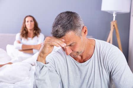 Close-up de deprimido hombre sentado en la cama delante de su esposa en casa Foto de archivo