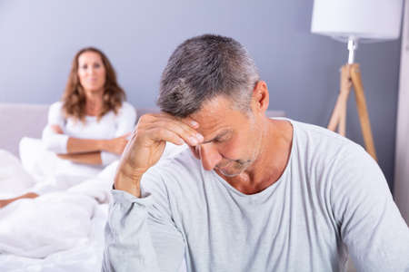 Close-up Of Depressed Man Sitting On Bed In Front Of Her Wife At Home
