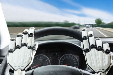 Close-up Of Robotic Hands On Cars Steering Wheel