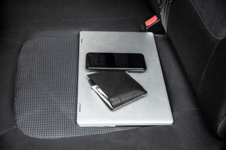 Mobile Phone And Laptop On Car's Seat Archivio Fotografico - 129473018