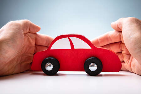 Businessman's Hand Protecting Red Toy Car On The Wooden Desk Archivio Fotografico - 129473047