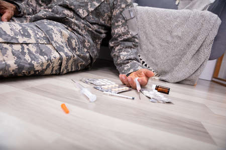 Syringe And Blister Packed Of Pills Fallen On Floor Near Disables Army Officer At Home 写真素材