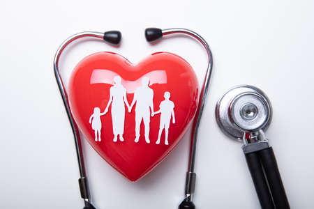 High Angle View Of Family Cut Out Over Red Heart Shape With Stethoscope Above Isolated