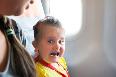 Little Girl Sitting Next To Mother Crying On Airplane