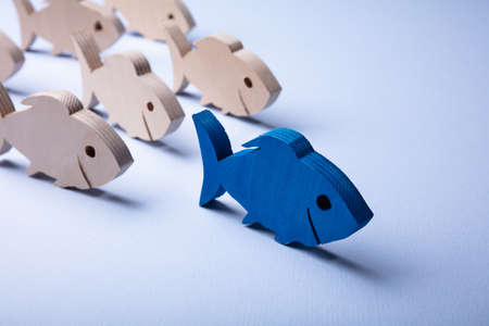 Close-up Of White Wooden Fishes Behind Blue Fish Over Colored Background